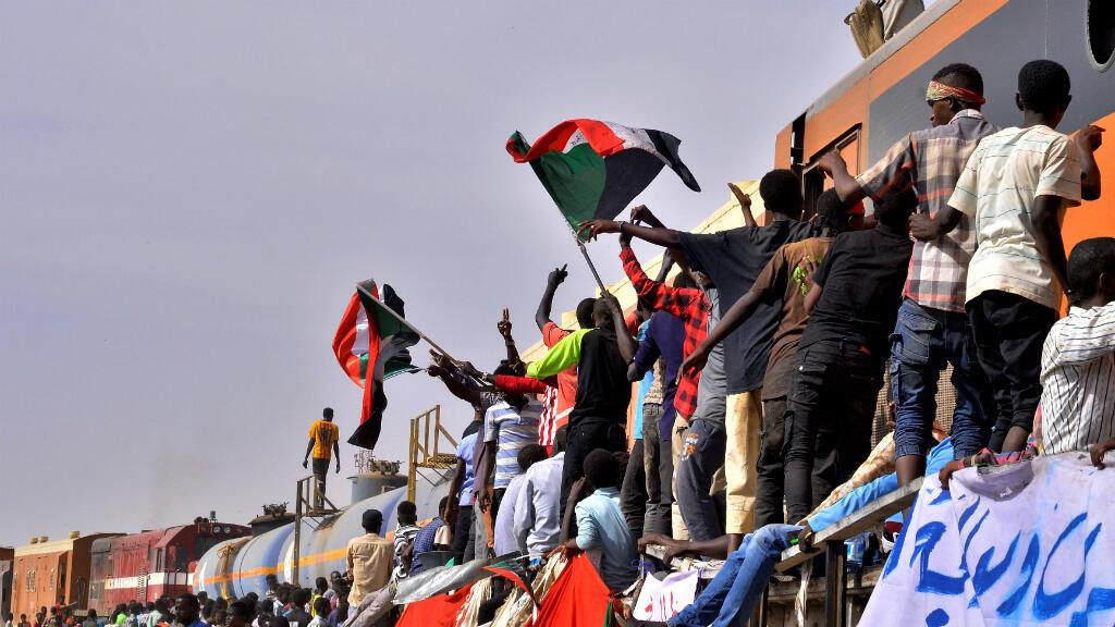 Manifestantes sudaneses que asisten a una protesta, se paran en un tren mientras bloquean el paso, fuera del Ministerio de Defensa en Jartum, Sudán, el 14 de abril de 2019.