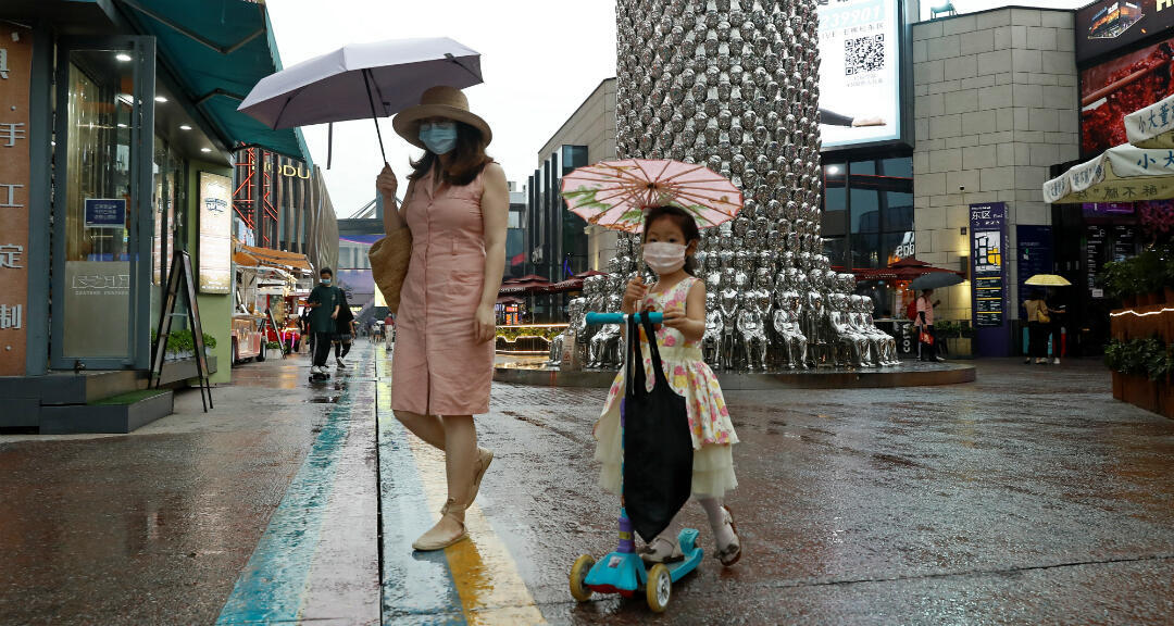 Una madre camina con su hija ambas llevando mascarillas en Beijing, China el 17 de julio de 2020.