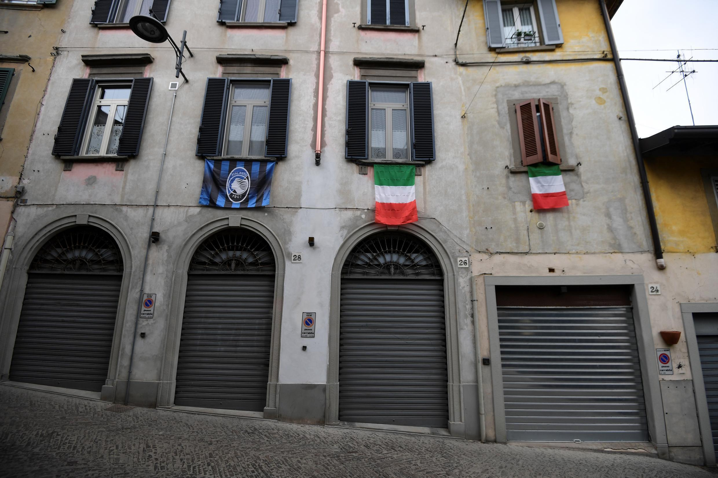 The flags of Italy and Atalanta hang over closed shops in a deserted street of Albino, near Bergamo.