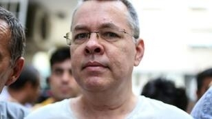 US pastor Andrew Brunson, seen here escorted by Turkish plainclothes police officers as he arrives at his house in Izmir, Turkey, was moved from prison to house arrest on July 25, 2018