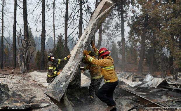 Los bomberos mueven escombros mientras recuperan restos humanos de un remolque destruido por el Camp Fire en Paradise, California , EE. UU., 17 de noviembre de 2018.
