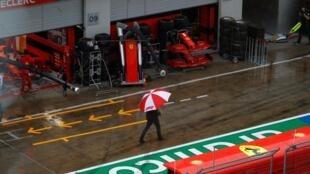 Un homme avec un parapluie devant les stands de Ferrari avant la 3e séance d'essais libres du Grand Prix de Styrie annulée en raison de la pluie le 11 juillet 2020 à Spielberg, en Autriche
