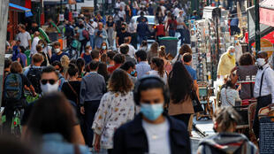 People wearing protective face masks walk in a busy street in Paris on September 18, 2020. France has reinforced measures to curb a resurgence of the coronavirus disease (Covid-19).