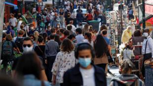 أشخاص يرتدون أقنعة واقية يسيرون في شارع مزدحم في باريس بينما تعزز فرنسا ارتداء الأقنعة في الأماكن العامة كجزء من الجهود المبذولة للحد من انتشار فيروس كورونا في جميع أنحاء فرنسا، 18 سبتمبر/ أيلول 2020.