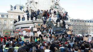 Manifestantes trepan sobre la Estatua de la República en medio de la manifestación para pedir medidas frente al cambio climático en París, Francia, el 16 de marzo de 2019.