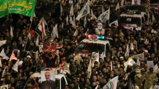 Des dizaines de milliers d'Irakiens ont formé un cortège funéraire, le 4 janvier 2019 dans la ville irakienne de Kerbala, autour des pick-up transportant la dépouille du général iranien Qassem Souleimani et des autres victimes tuées dans un raid américain, la veille.