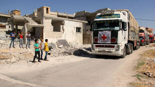 Des enfants syriens sur la bas côté de la route regardant le passage de camions de la Croix rouge, le 26 juillet 2016, à Tablisseh.