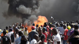 People stand in front of smoke rising from the Burkina Faso's parliament building in Ouagadougou