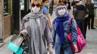 سيدتان ترتديان أدوات واقية للحماية من فيرو كورونا اثناء تسوقهما في تجريش في طهران في 25 نيسان/ابريل 2020.
