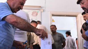 A Syrian man casts his ballot at a polling station in an Aleppo neighbourhood during parliamentary elections