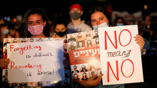 Women hold placards during a protest against sexual violence in Tel Aviv on August 23, 2020.