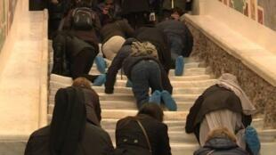 Capture d'écran d'une vidéo de l'AFPTV filmant, le 12 avril 2019 à Rome, des pèlerins gravissant à genoux l'escalier qu'aurait emprunté le Christ avant de comparaître devant Ponce Pilate