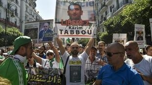 An Algerian protester marches with a sign calling to set free politician Karim Tabbou during a demonstration against the ruling class in the capital Algiers on September 27, 2019 for the 32nd consecutive Friday since the movement began.