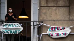 Une femme applaudit les soignants depuis le balcon de son appartement à Saint-Mandé, en banlieue parisienne, le 4 mai 2020  à20h