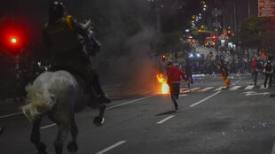 Demonstrators run as mounted police chase them during a protest against police brutality in Medellin, Colombia, on September 10, 2020.