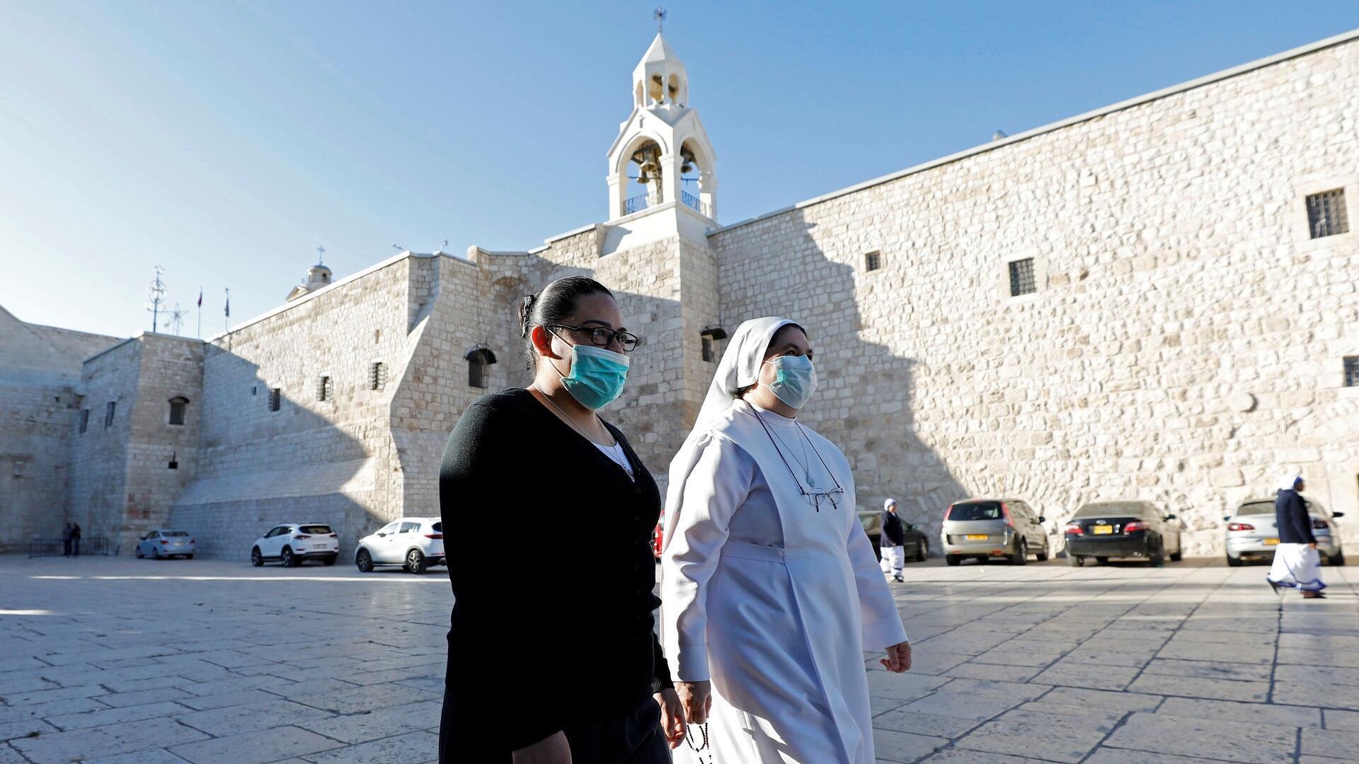 راهبة مسيحية وسيدة ترتديان كمامتين وتمران أمام كنيسة المهد في بيت لحم بالضفة الغربية، 26 مايو/أيار 2020.
