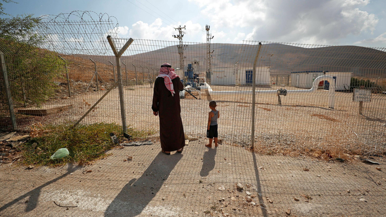 Los palestinos se paran junto a una valla mientras miran las tuberías de agua israelíes en el valle del Jordán, en la Cisjordania ocupada por Israel el 21 de agosto de 2019.