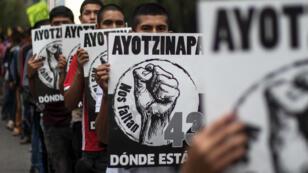 Activistas marchan para conmemorar el tercer aniversario de la desaparición de los 43 estudiantes de la escuela de formación de docentes en Ayotzinapa desaparecidos en septiembre de 2014 en Iguala, en el estado de Guerrero, suroeste del país, tras enfrentamientos con la policía en la Ciudad de México el 26 de septiembre de 2017.