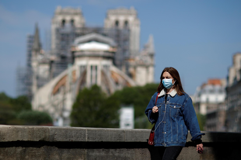 A woman, wearing a protective face mask, walks past Notre-Dame de Paris Cathedral in Paris, France on April 27, 2020.