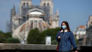 امرأة ترتدي قناع وجه واقٍ، تمشي أمام كاتدرائية نوتردام دي باريس، باريس، فرنسا ، 27 أبريل 2020.