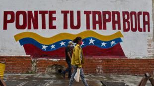 """Peatones caminan con sus máscaras faciales delante de un grafiti que señala """"Ponte tu tapaboca"""", el 21 de julio de 2020 en el centro de Caracas"""
