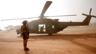 جندي فرنسي أمام مروحية من طراز كايمان من قوة برخان، في نداكي، مالي، 29 يوليو/ تموز 2019.