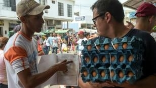 Giovanni Jose Plaza (L), a Venezuelan migrant suffering from AIDS, asks passersby in the border town of Cucuta, Colombia for money to buy medications