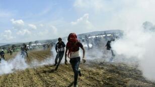 لاجئون يهربون من الغاز المسيل للدموع خلال مواجهات مع قوات الأمن المقدونية 10 نيسان/أبريل 2016