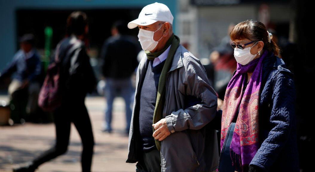 Una pareja con tapabocas camina por las calles de Bogotá, Colombia. 17 de marzo de 2020.