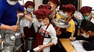 Students wearing face masks as a preventive measure to curb the spread of the COVID-19 coronavirus collect their lunch at an elementary school in Taipei in April 2020
