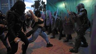 Una mujer se enfrentan con la policía antidisturbios durante el cuarto día consecutivo de protestas contra la brutalidad policial, el 12 de septiembre de 2020 en Bogotá