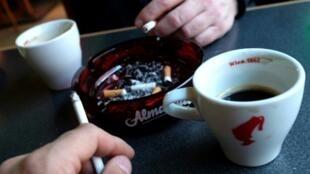 Clientes en un bar fuman cigarrillos con su café, en Viena el 22 de marzo de 2018