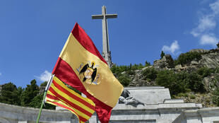 Una bandera franquista alzada frente al Valle de los Caídos durante una manifestación de ultraderecha en contra de la exhumación de los restos de Franco en San Lorenzo del Escorial, España, el 15 de julio de 2018.