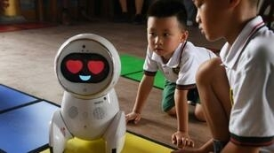 Children watch a Keeko robot at the Yiswind Institute of Multicultural Education in Beijing, where the intelligent machines are telling stories and challenging kids with logic problems