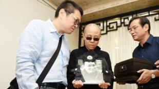 La poétesse Liu Xia, 57 ans, tenant entre ses mains un portrait de son défunt époux Liu Xiaobo.