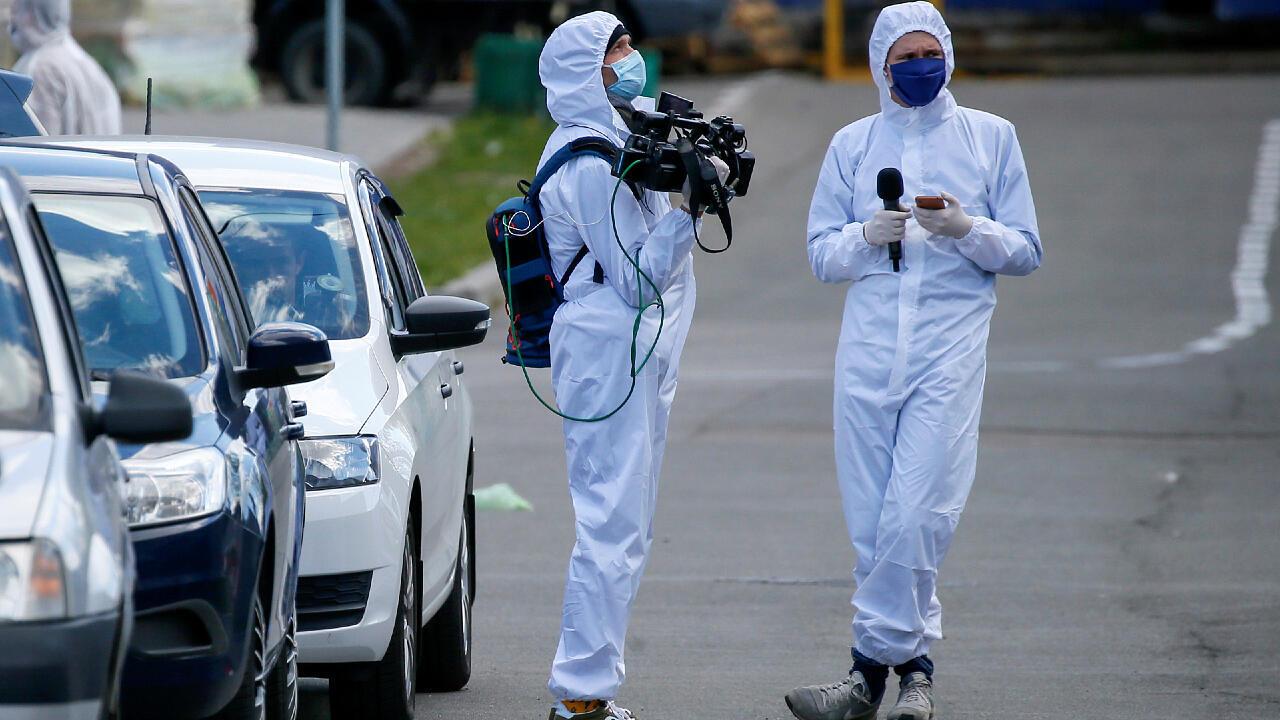 Dos periodistas utilizan equipos de protección personal para cubrir una noticia el 28 de abril de 2020 de un hostal que cerraron en Kiev, Ucrania, luego de que los residentes dieran positivo por Covid-19.
