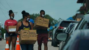 متطوعون يوزعون الطعام على مدخل مركز لفحص فيروس كورونا المستجد في دالاس بولاية تكساس في 29 تموز/يوليو 2020