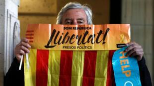 Manifestante sostiene la bandera catalana mientras espera la llegada del expresidente catalán en Bélgica el 17 de noviembre de 2017..