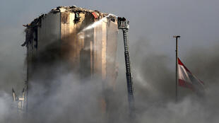 Lebanese firefighters use a ladder to hose down the warehouses and silos of Beirut port after Thursday's blaze