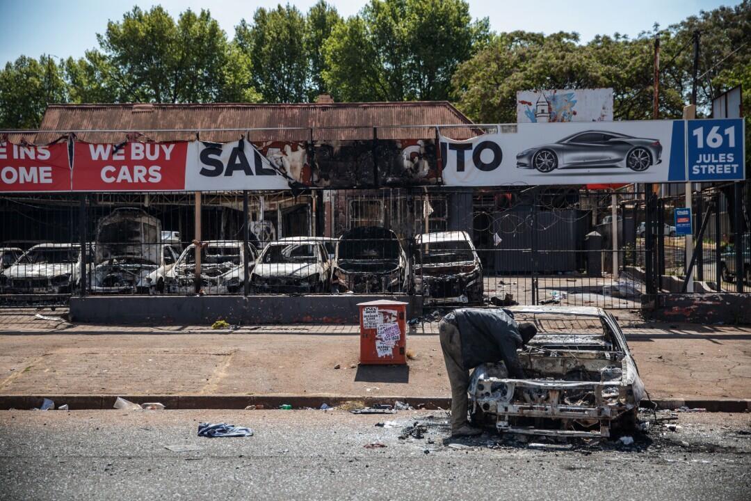 Un homme fouille dans une voiture incendiée à Malvern, dans la banlieue de Johannesburg, le 4 septembre 2019, après une nouvelle vague de violences xénophobes.