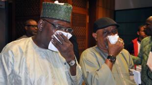 Des députés nigérians se couvrent la bouche et le nez après des tirs de gaz lacrymogène dans l'entrée du Parlement.