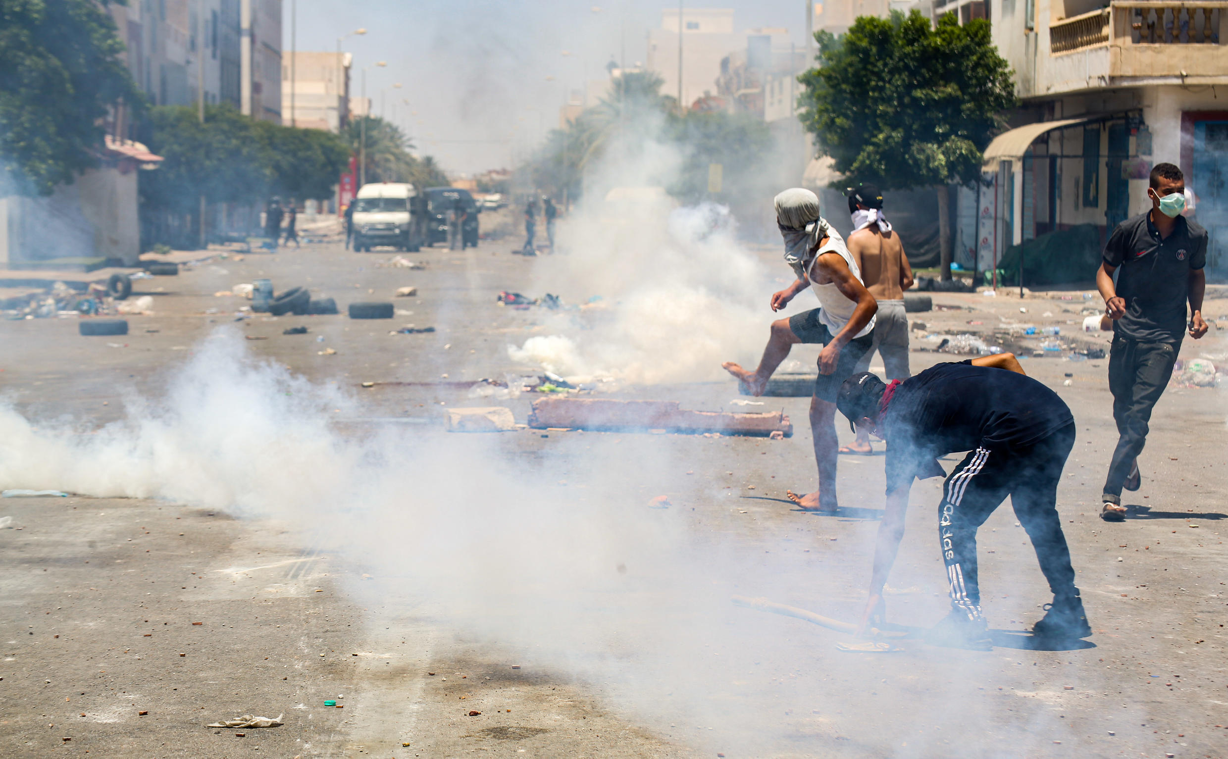 Protesters from Tunisia's Tataouine region throw stones as they clash with security forces, firing tear gas, amidst a demonstration in the southern city on June 21, 2020.