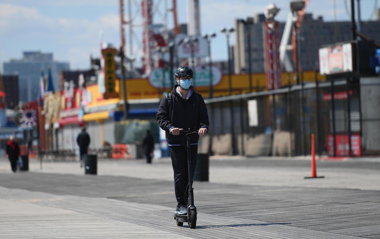 Un neoyorquino con máscara se transporta en monopatín el 15 de abril de 2020 en Coney Island, Nueva York
