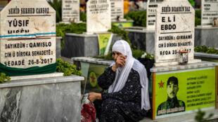 سيدة مسنّة تبكي عند قبر ابنها المقاتل في صفوف قوات سوريا الديموقراطية في 23 أيار/مايو 2020 في مدينة القامشلي في شمال شرق سوريا