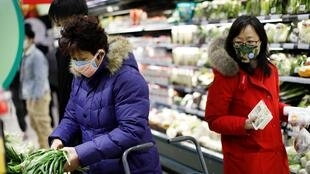 People wearing face masks look for products at a supermarket, as the country is hit by an outbreak of the new coronavirus, in Beijing, China January 31, 2020.