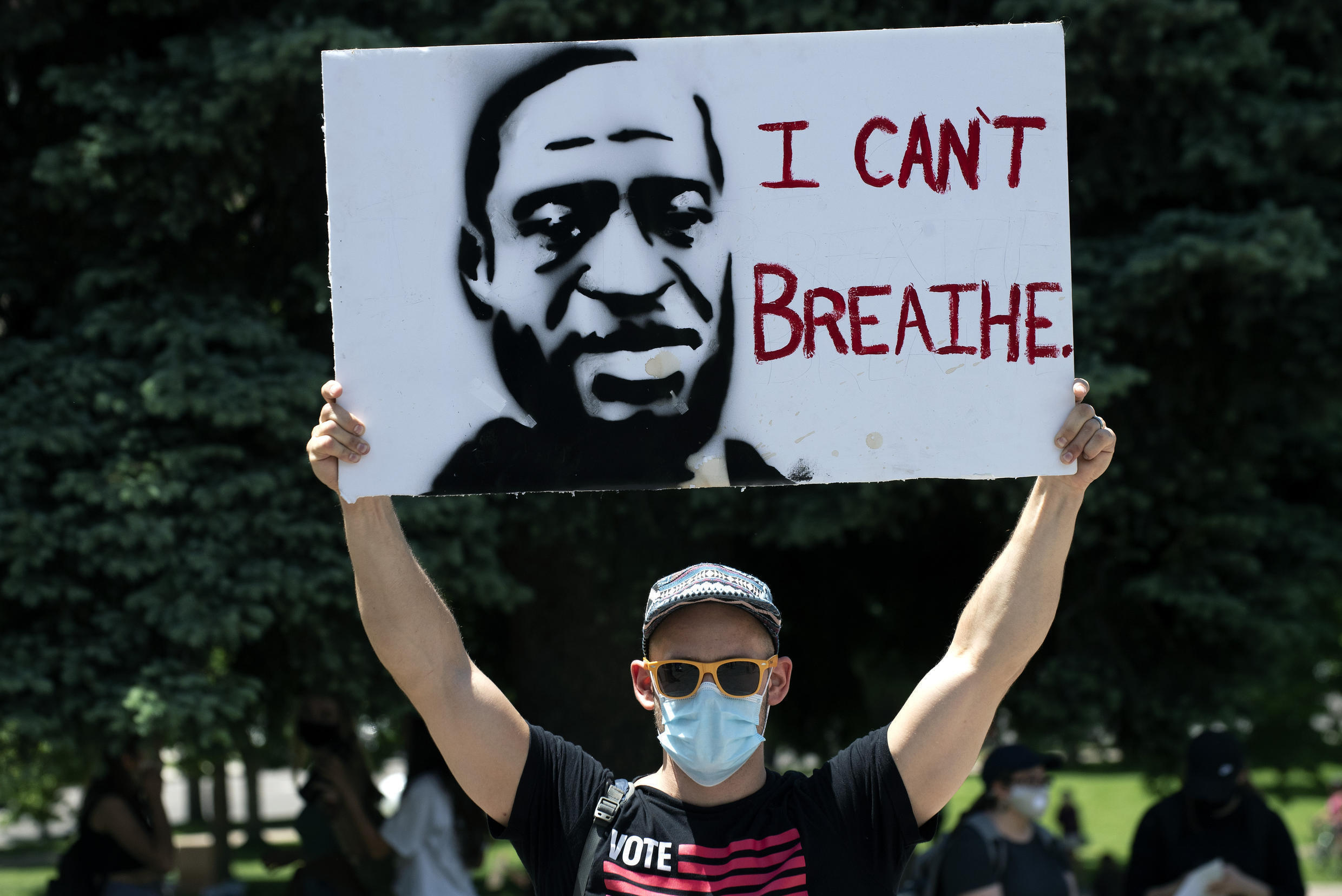 A protester holds up a poster with a portrait of George Floyd on May 30 in Denver.