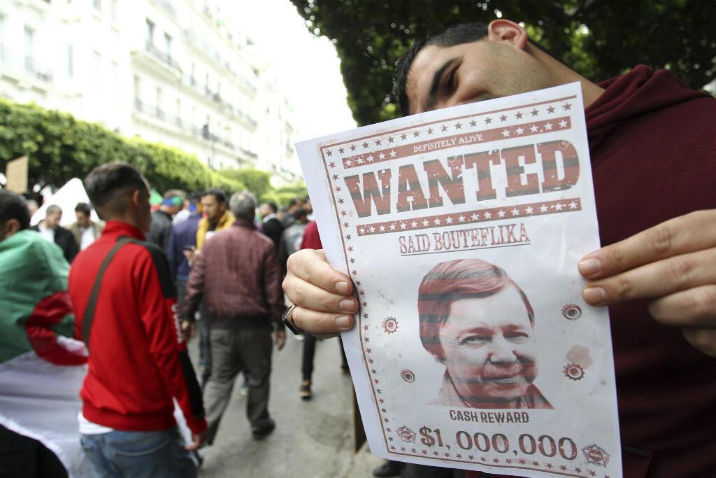 """Un manifestant présente une affiche """"recherché"""", montrant Saïd Bouteflika, le frère du président déchu, lors d'une manifestation anti-pouvoir à Alger, le 19 avril 2019."""