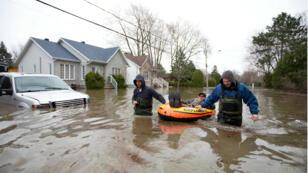 Un hombre es asistido durante las evacuaciones por las inundaciones en Sainte-Marthe-sur-le-Lac, Quebec, el 28 de abril de 2019.