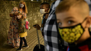 A group of young students wearing face masks to prevent the spread of the coronavirus wait outside with adults to enter a state school in Pamplona, northern Spain, on September 4, 2020.