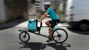 A Deliveroo cyclist in Paris, where staff at several food delivery services have called a strike seeking better pay and benefits